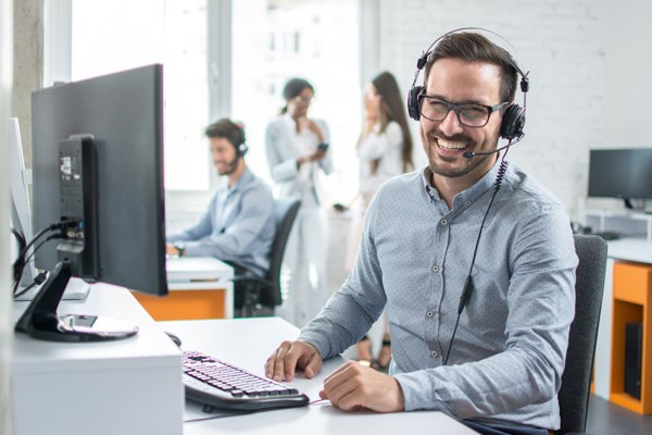 Smiling male support desk worker wearing headphones with colleagues in background.